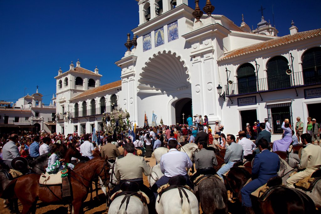 El Rocio, Huelva, Southern Spain. Man in traditional clothes on horseback in front of the main church in the village of El Rocio during the annual Romeria : Stock Photo