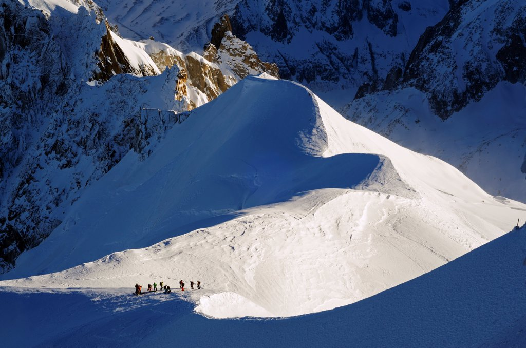Europe, France, French Alps, Haute Savoie, Chamonix, Aiguille du Midi, skiers walking down the ridge at the start of Vallee Blanche off piste : Stock Photo