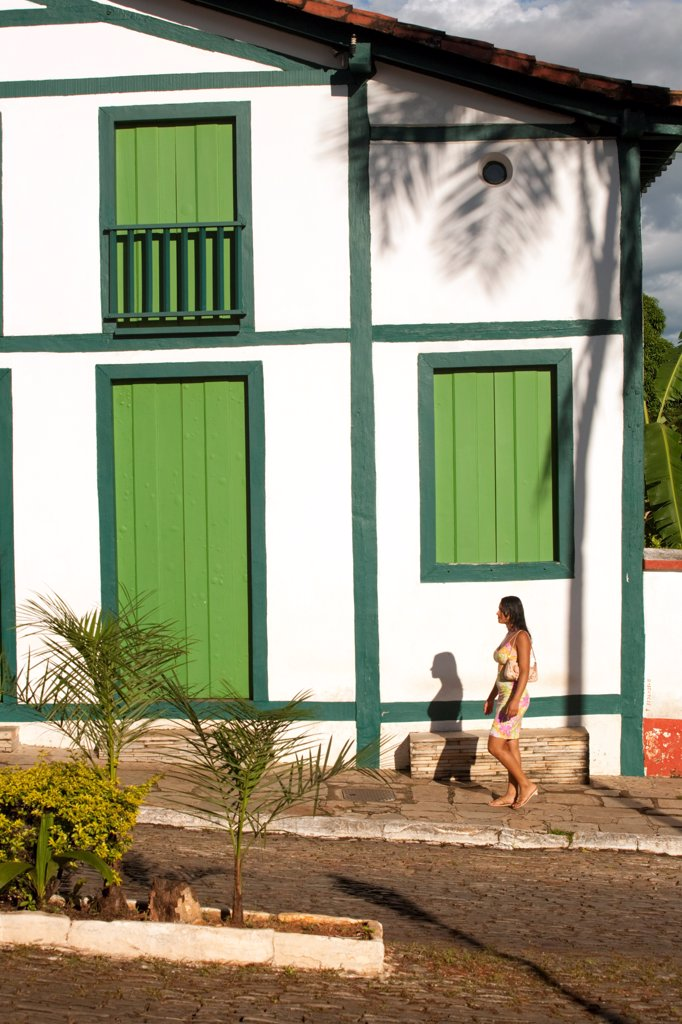 South America, Brazil, Goias, Pirenopolis, a woman walks past Portuguese colonial houses on the Rua Nossa Senhora do Rosario in the mining town of Pirenopolis near Brasilia : Stock Photo