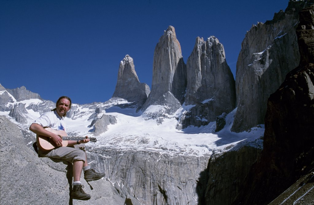 Stock Photo: 4272-6102 Playing guitar in front of the Towers of Paine