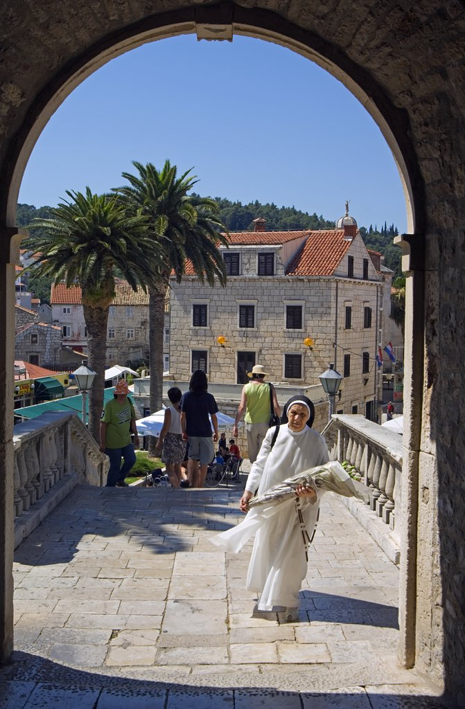 Stock Photo: 4272-6774 Korcula Island Nun walking through Gate of Medieval Old Town City Wall