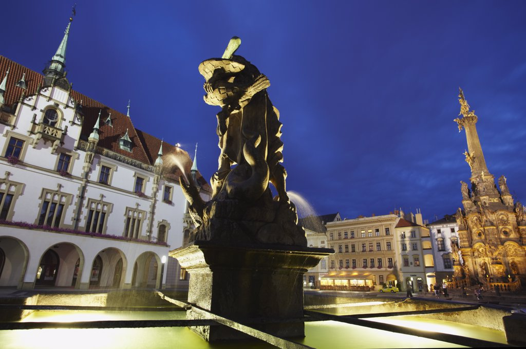 Stock Photo: 4272-7163 Czech Republic, Moravia, Olomouc, Fountain In Front Of Town Hall In Upper Square (Horni Nam) At Dusk With Holy Trinity Column In Background