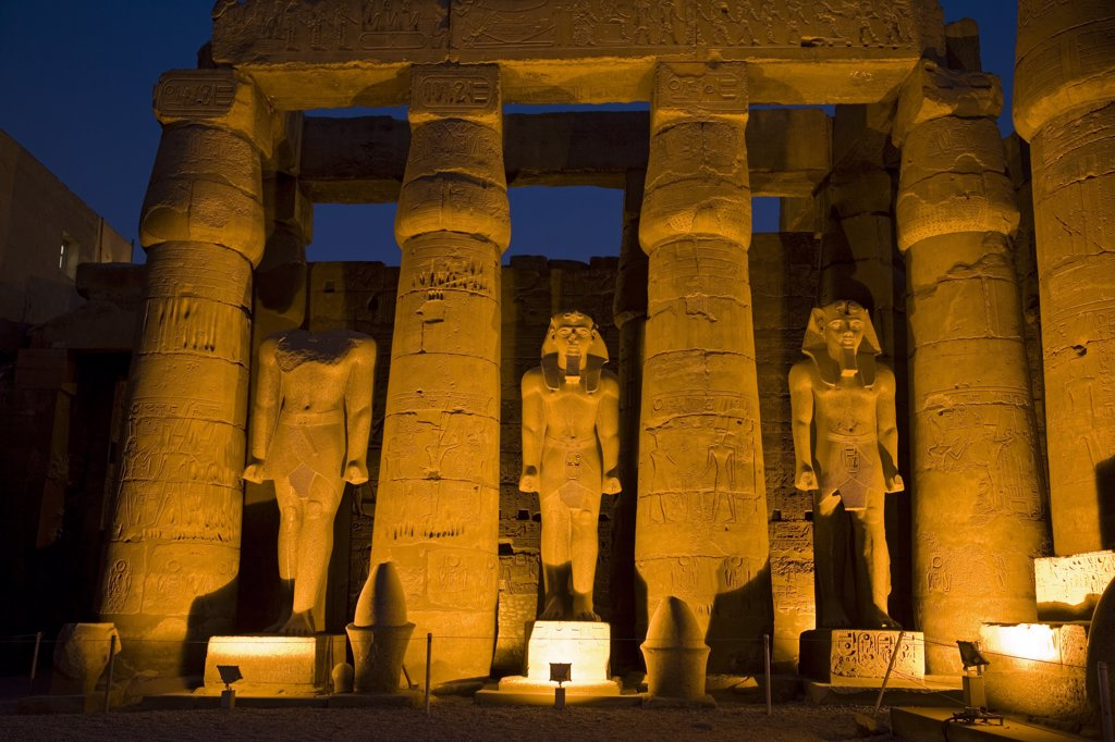 Larger than life statues of Ramses II illuminated at night in Luxor Temple, Egypt : Stock Photo