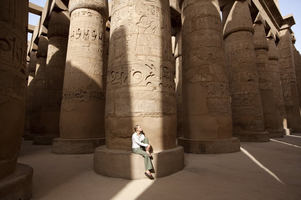 Stock Photo: 4272-7783 Egypt, Karnak. A tourist sits at the base of a massive stone column in the Great Hypostyle Hall. (MR)