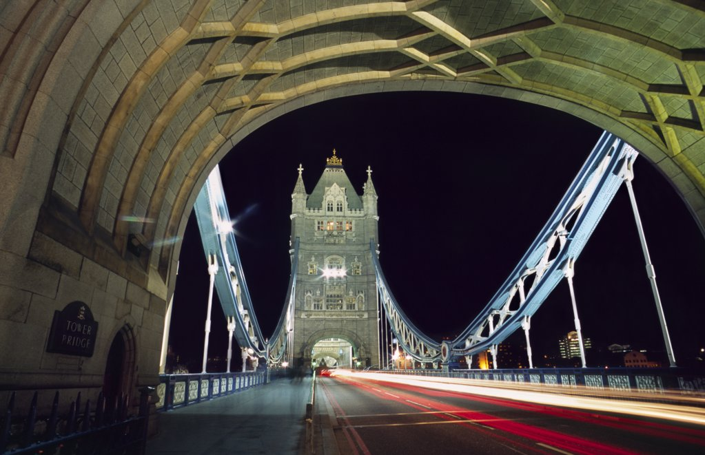 Stock Photo: 4272-8398 Night time traffic crosses Tower Bridge in central London. Built in 1894, the iconic bridge was designed to rise and allow ship to pass through.