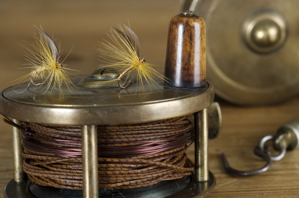 England.  Dry flies on a traditional brass fly fishing reel. : Stock Photo