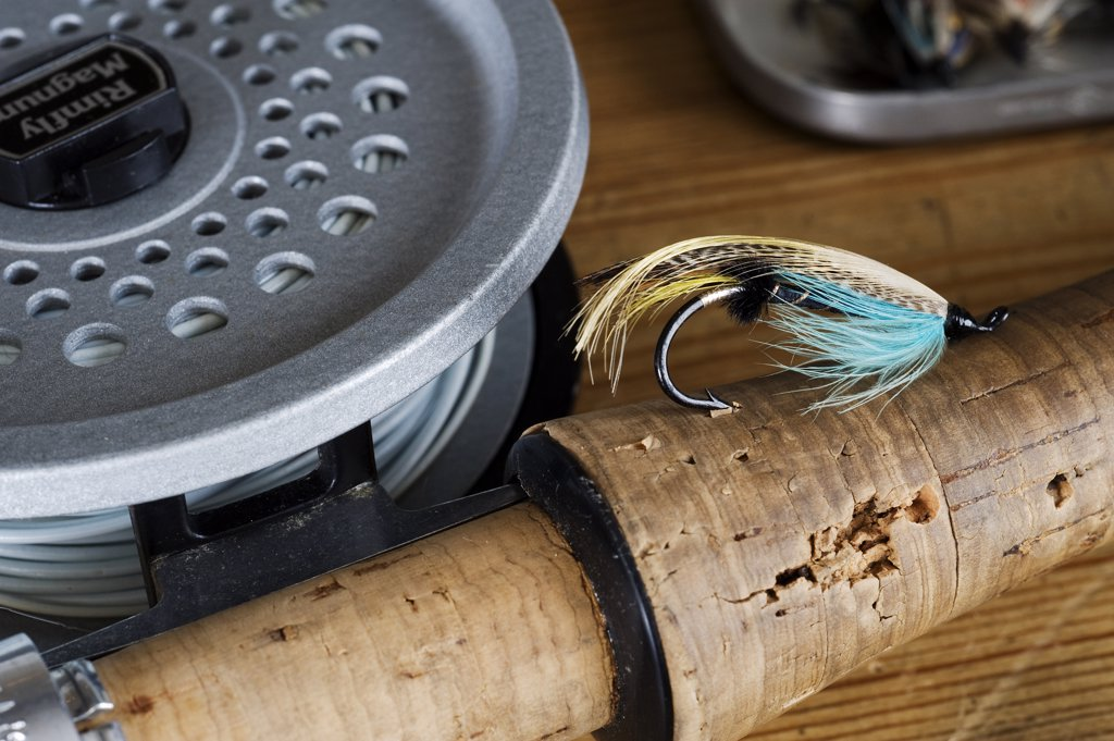 Stock Photo: 4272-9164 UK.  A salmon fly stuck into the cork handle of a fly fishing rod.