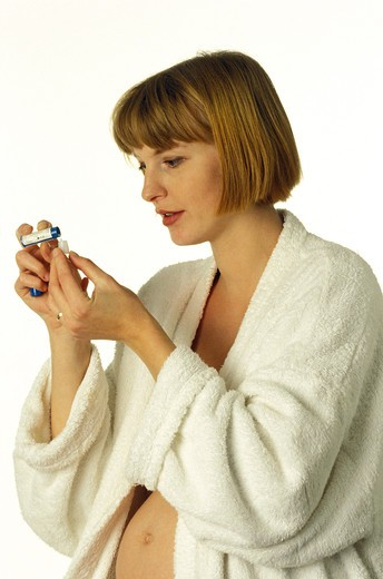 Pregnant Woman In Bath Robe Taking Homeopathic Pills Against White Background : Stock Photo