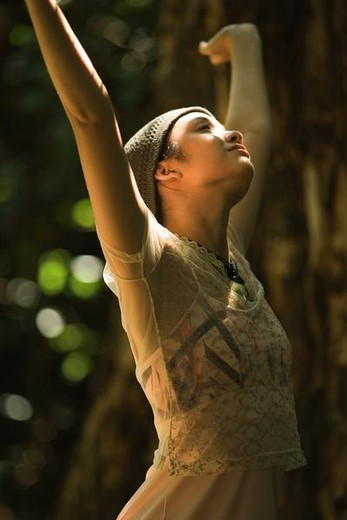 Stock Photo: 4276-1008 Young woman standing outdoors with arms raised, looking up, side view