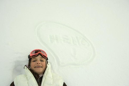 """Stock Photo: 4276-1057 Teenage girl lying on snow next to thought bubble and the word """"hello"""", smiling at camera"""