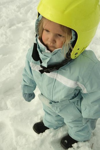 Stock Photo: 4276-1063 Toddler girl standing in snow, dressed in winter clothing and ski helmet, high angle view