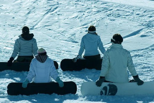 Stock Photo: 4276-1065 Four young snowboarders sitting on ski slope, rear view
