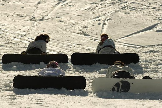 Stock Photo: 4276-1066 Four young snowboarders sitting on ski slope, rear view, one looking over shoulder