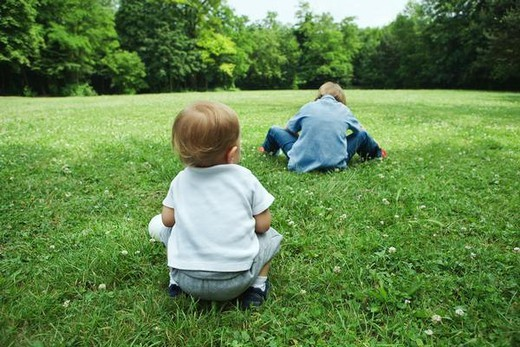 Stock Photo: 4276-1079 Baby boy crouching in grass, watching older sibling, rear view
