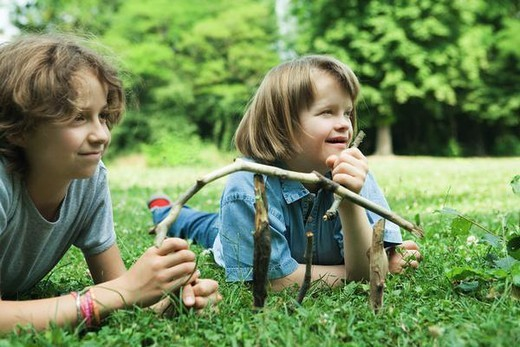 Stock Photo: 4276-1088 Two girls lying on grass, holding sticks, smiling, one with Down's Syndrome