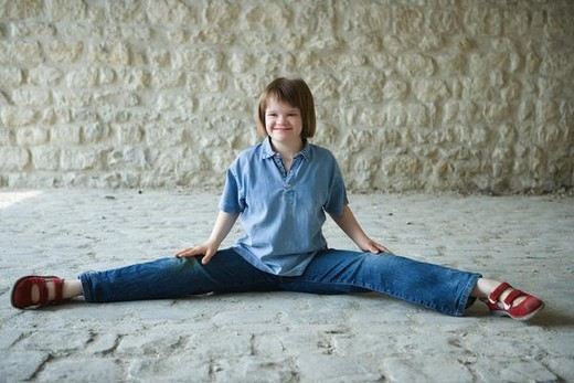 Girl with Down's Syndrome doing split on the ground, smiling, looking away : Stock Photo