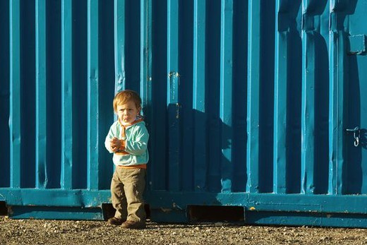 Stock Photo: 4276-1172 Little boy standing outdoors, frowning, looking away
