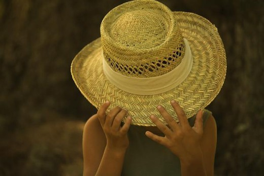 Stock Photo: 4276-1216 Little boy pulling straw hat over face, portrait