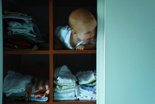 Stock Photo: 4276-1231 Baby boy peeking out of shelf, looking away