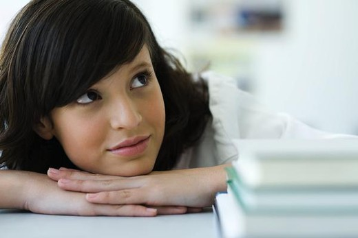Stock Photo: 4276-1291 Young female resting head on hands, looking up dreamily, stack of books in foreground
