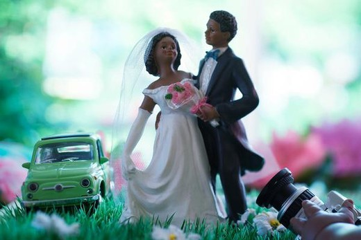Bride and groom figurines posing in field of fake flowers, hand holding camera in foreground : Stock Photo