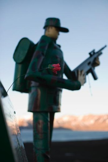 Soldier figurine holding rifle, focus on single artificial rose in foreground : Stock Photo