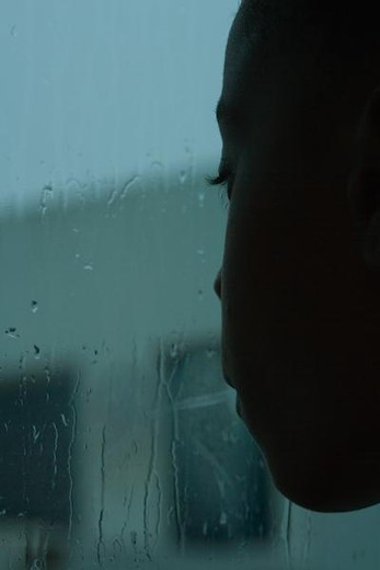 Stock Photo: 4276-1459 Girl looking out window on rainy day, close-up
