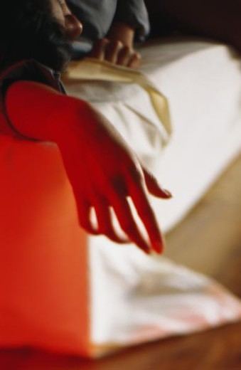 Stock Photo: 4276-1593 Person lying on bed, close-up of hand hanging off corner of bed