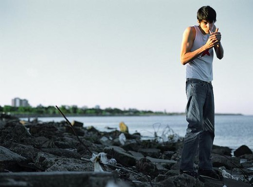 Young man smoking on junk-ridden rocky shore : Stock Photo