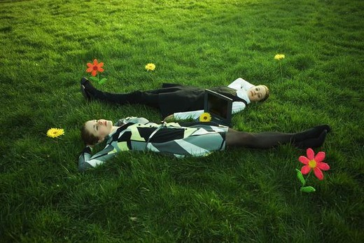 Stock Photo: 4276-1724 Two females lying in grassy field with flowers, laptop computer on the ground between them, one looking at camera