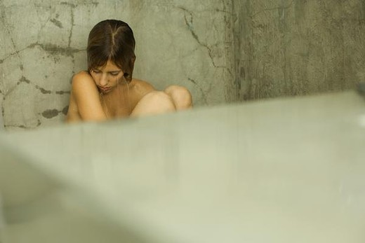 Nude female sitting in shower, head down, eyes closed : Stock Photo