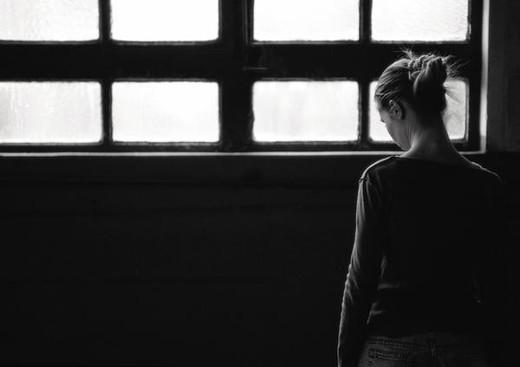 Woman standing near window, rear view : Stock Photo