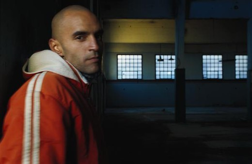 Young man wearing jacket in warehouse, looking at camera : Stock Photo