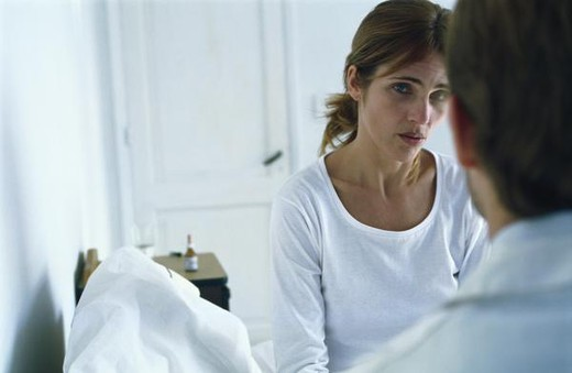 Stock Photo: 4276-1907 Woman sitting on bed with concerned expression, speaking to doctor