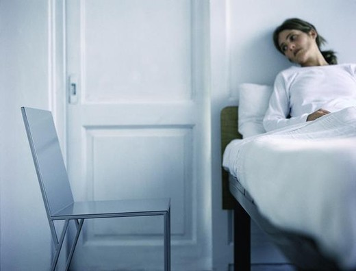 Woman reclining in bed, looking at door, empty chair nearby : Stock Photo