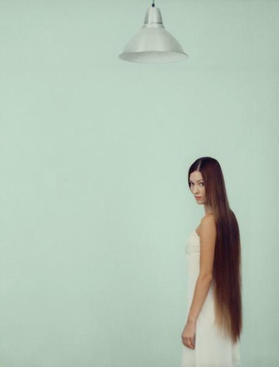 Stock Photo: 4276-2012 Young woman with long hair, looking over shoulder at camera