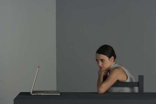 Stock Photo: 4276-2028 Woman sitting at table with hand under chin, looking at laptop computer