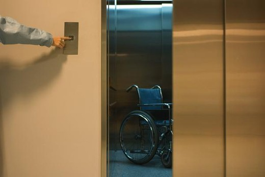 Person pressing button to open elevator, empty wheelchair inside, cropped view : Stock Photo