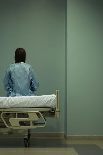 Stock Photo: 4276-2043 Female patient sitting on hospital bed, facing wall, rear view
