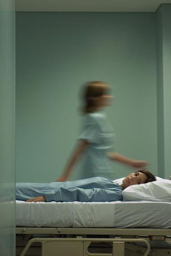 Woman lying on hospital bed, looking at camera, nurse walking by in background : Stock Photo