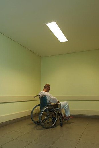 Male patient sitting in wheelchair, head down : Stock Photo