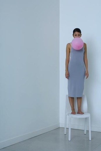 Woman standing on chair, holding balloon in mouth, looking at camera : Stock Photo