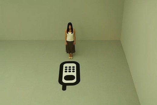 Woman standing before large cell phone, looking down, high angle view : Stock Photo