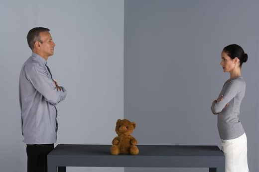 Couple standing face to face at table, arms folded, teddy bear between them : Stock Photo