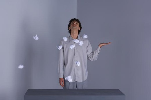 Man standing with hand out, looking up, paper balls in mid-air around him : Stock Photo