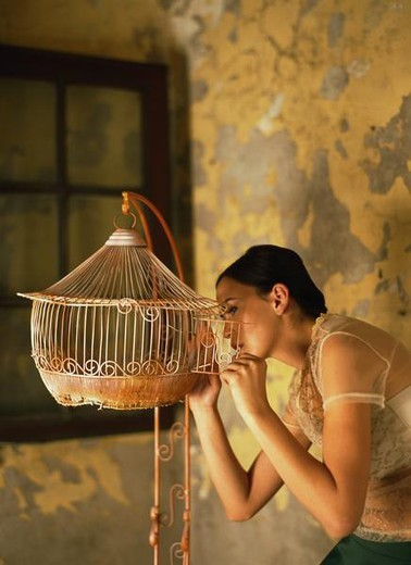 Woman looking inside empty birdcage, side view : Stock Photo