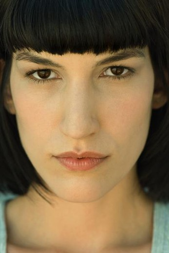Portrait of young woman looking at camera, close-up : Stock Photo