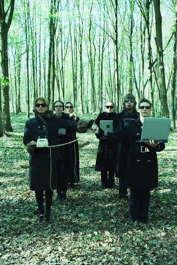 People dressed all in black lined up in woods, holding laptop computers and landline phones, front view : Stock Photo