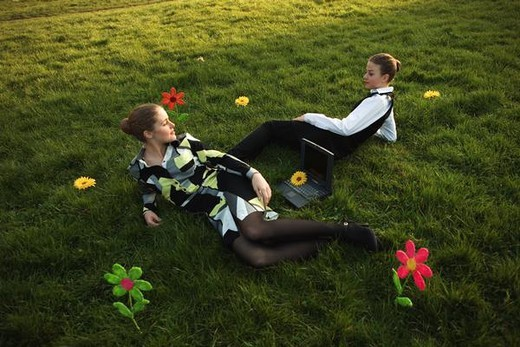 Two females lying in grassy field with laptop computer between them : Stock Photo