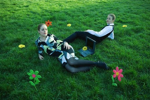 Stock Photo: 4276-2472 Two females lying in grassy field with laptop computer between them, one looking over shoulder at camera
